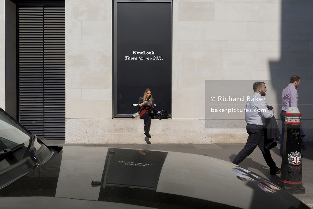 A young woman eats a quiet lunch outside clothing retailer new Look on Lombard Street in the City of London, the capital's financial district also known as the Square Mile, on 6th April 2017, in London, England.