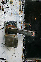 Rusty old brass padlock on door of garden shed
