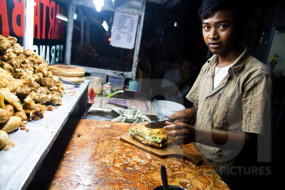 A boy makes a traditional streetside snack in Bali, Indonesia, Southeast Asia
