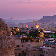 Goreme village at sunrise with hot air balloons, Cappadocia