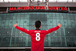 © Licensed to London News Pictures . 27/01/2014 . Manchester , UK . DANIEL LEE (23, from Hong Kong and studying at Warwick University) poses with his new shirt in front of Old Trafford . Fans with new MATA 8 shirts in front of Old Trafford Football Ground as it's announced that Spaniard Juan Mata ( Juan Manuel Mata García ) has signed for Manchester United  . Photo credit : Joel Goodman/LNP