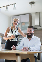 Portrait of a young couple with digital tablet in the kitchen and smiling, Bavaria, Germany