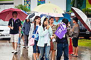 26 JUNE 2011 - CHIANG MAI, THAILAND:  People walk in the rain to absentee voting center in Chiang Mai, Thailand, Sunday. Absentee voting was Sunday, July 26 in Thailand's national election. The regular voting is Sunday July 3. In Chiang Mai, center of the powerful Red Shirt opposition movement and their legal party Pheua Thai, turnout was heavy despite a steady rain. Thailand's democracy will be tested in the election, which is the most bitterly fought contest in Thai political history. The Pheua Thai represents people loyal to fugitive former Prime Minister Thaksin Shinawatra, ousted by a military coup in 2006. The ruling Democrats have governed Thailand in one form or another nearly continuously since 1932. Pre-election polls show Pheua Thai leading but not by enough to rule without forming a coalition with smaller parties.  PHOTO BY JACK KURTZ