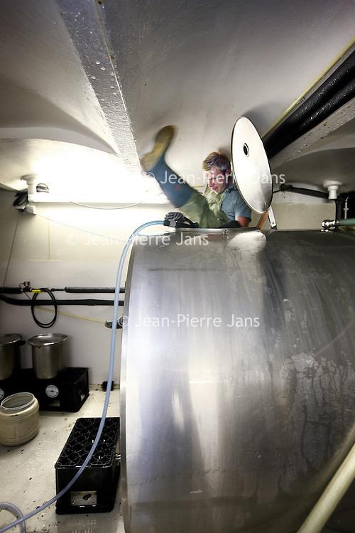 Nederland, Amsterdam , 1 juli 2010..Bierbrouw proces in bierbrouwerij t IJ..Brouwerij 't IJ is een kleine lokale Amsterdamse bierbrouwerij, sinds oktober 1985 gevestigd in voormalig badhuis Funen, naast Molen De Gooyer. De brouwerij wordt geleid door Kaspar Peterson. Alle bieren zijn gemaakt van 'biologische' grondstoffen en door SKAL[1] gecertificeerd. De brouwerij heeft ook een proeflokaal, dat alleen IJ-bier schenkt. In tegenstelling tot veel andere proeflokalen wordt het IJ-lokaal ook veel als stamkroeg gebruikt..Om de tanks schoon te spuiten van binnen moet je helemaal in de tank kruipen..Cleaning the cauldron of the beer in Brouwerij 't IJ, a small local brewery in Amsterdam since 1985, producing very nice beer. The cleaner has to climb into the cauldron in order to clean it.