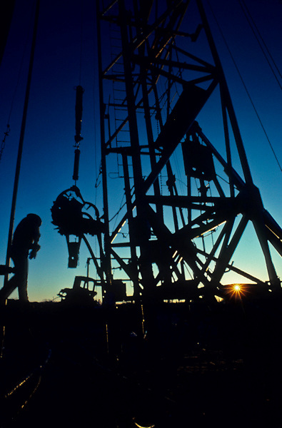 Stock photo of the silhouette of men working on an on-shore drilling rig.