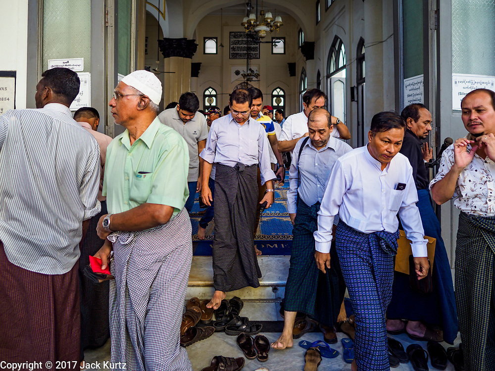 """24 NOVEMBER 2017 - YANGON, MYANMAR: Men leave Mogul Shiah Mosque in Yangon after Friday midday prayers. Many Muslims in overwhelmingly Buddhist Myanmar feel their religion is threatened by a series of laws that target non-Buddhists. Under the so called """"Race and Religion Protection Laws,"""" people aren't allowed to convert from Buddhism to another religion without permission from authorities, Buddhist women aren't allowed to marry non-Buddhist men without permission from the community and polygamy is outlawed. Pope Francis is to arrive in Myanmar next week and is expected to address the persecution of the Rohingya, a Muslim ethnic minority in western Myanmar. Some Muslims and Christians are concerned that if the Pope's comments take too strong of pro-Rohingya stance, he could exacerbate religious tensions in the country.  PHOTO BY JACK KURTZ"""