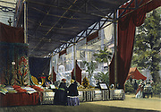 Great Exhibition, Hyde Park, London, 1851. Interior view of the Crystal Palace showing two visitors being shown a stand of oriental products. In the right hand front corner a man and woman admire plants in a Wardian case.  Coloured engraving.