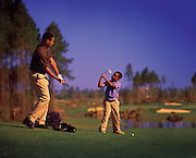 A father teaches his son how to swing a golf club