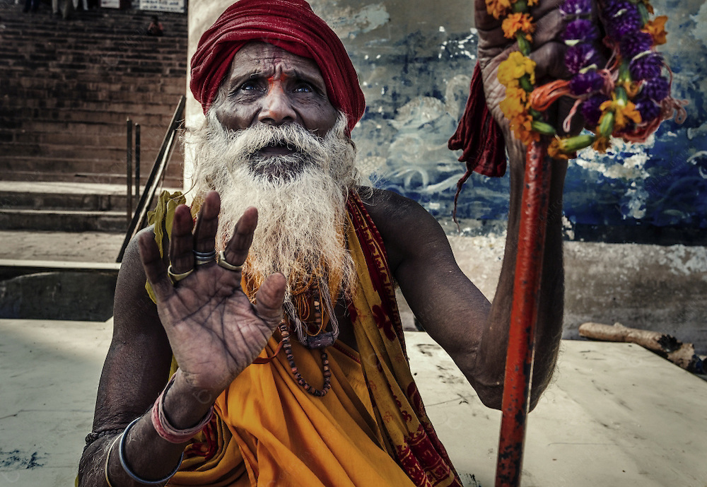 Varanasi, India - October 05, 2015: Man dressed as holy sadhu in Dashashwamedh Ghat in Varanasi. This is one of the oldest inhabited cities in the world and also the holiest of the seven sacred cities in Hinduism and Jainism and so the most important pilgrimage place for hindus. Many men dress as saddhus and beg for money to the thousands of pilgrims that visit the ghats everyday.