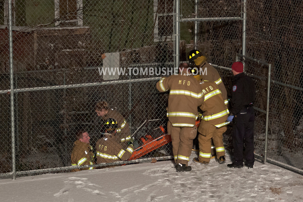 Middlletown, New York - Middletown firefighters carry an injured driver to an ambulance at the scene of a motor vehicle accident on Dec. 31, 2013. A vehicle went through a fence and landed upside down in a play area at the former Memorial School. A snow mage Workssquall had left the roads very slippery.