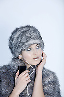 studio shot portrait of a beautiful woman russian type in a fur coat and hat studio shot portrait of a beautiful woman russian type in a fur coat and hat using her multimedia player listening music