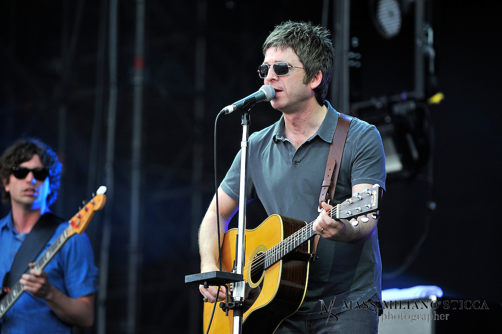 Noel Gallagher's High Flying Birds<br /> Noel Thomas David Gallagher (born 29 May 1967) is an English musician, singer and songwriter, formerly the lead guitarist, occasional lead singer and principal songwriter of Oasis. He is currently fronting his solo project, Noel Gallagher's High Flying Birds. Raised in Burnage, Manchester, Gallagher began learning guitar at the age of thirteen. After a series of odd jobs in construction, he worked for local Manchester band Inspiral Carpets as a roadie and technician in 1988. Whilst touring with them, he learned that his brother Liam Gallagher had formed a band of his own, known as The Rain, which eventually took on the name Oasis. After Gallagher returned to England, he was invited by his brother to join Oasis as songwriter and guitarist.