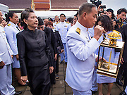19 OCTOBER 2014 - BANG BUA THONG, NONTHABURI, THAILAND: RATCHANEE WIRIYACHAI, (left) widow of Apiwan Wiriyachaiat, follow representatives of the Palace into the cremation ceremony for her husband, Apiwan Wiriyachai at Wat Bang Phai in Bang Bua Thong, a Bangkok suburb, Sunday. Apiwan was a prominent Red Shirt leader. He was member of the Pheu Thai Party of former Prime Minister Yingluck Shinawatra, and a member of the Thai parliament and served as Yingluck's Deputy Prime Minister. The military government that deposed the elected government in May, 2014, charged Apiwan with Lese Majeste for allegedly insulting the Thai Monarchy. Rather than face the charges, Apiwan fled Thailand to the Philippines. He died of a lung infection in the Philippines on Oct. 6. The military government gave his family permission to bring him back to Thailand for the funeral. His cremation was the largest Red Shirt gathering since the coup.     PHOTO BY JACK KURTZ