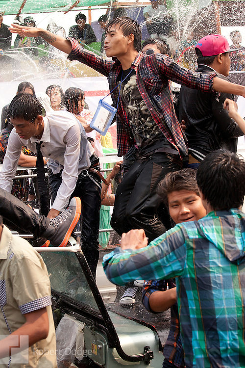 Mandalay, Myanmar- April 14, 2013: Young men climb atop a moving vehicle to dance and get hosed by water during Myanmar's Thingyan Water Festival. Thingyan is held in April, one of the hottest months of the year in Myanmar. The water festival marks the country's New Year celebration and the festival includes lots of drinking, singing, dancing and theater. Wherever you are you are likely to get doused with water as the Burmese see this as a cleansing of the previous year's sins and bad luck and a blessing for good luck and prosperity in the year ahead. In the major cities of Mandalay and Yangon, large platforms are erected along major roadways and are equipped with high powered water hoses. The platforms, sponsored by large corporate donors, also have dance stages and play the latest pop and hip hop music. Thousands of residents pour into the streets by foot, motorbike and flatbed truck to get hosed under the platforms while they drink and dance. Many of the young celebrants wear their best clubbing clothes. And many of the party goers are men, having left their wives and girlfriends at home.