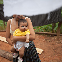 A young woman carries a baby between washing lines in Concepción Actelá, Alta Verapaz