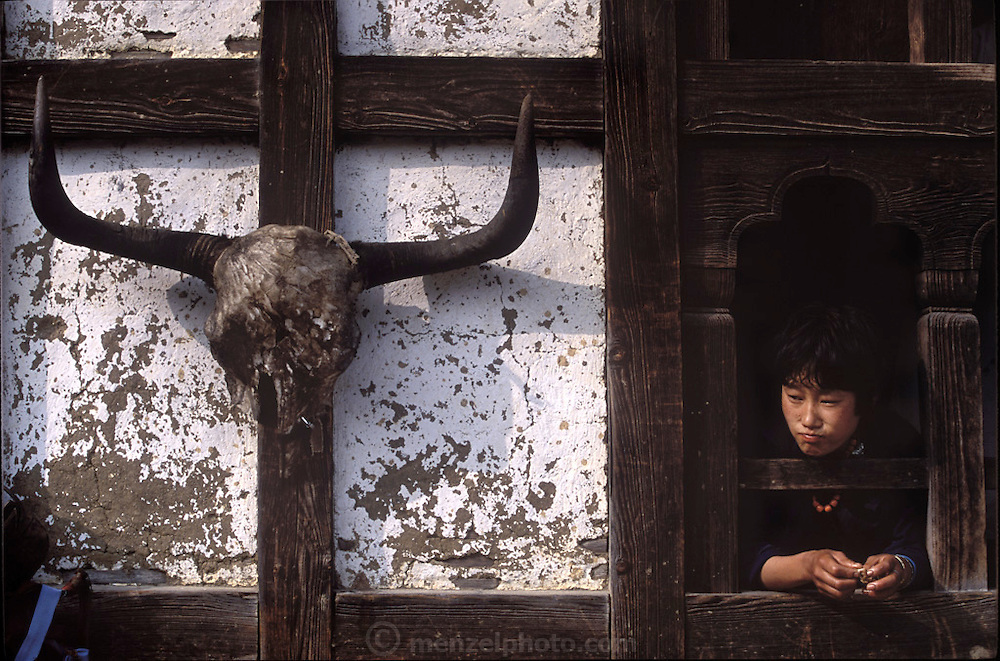 (MODEL RELEASED IMAGE). Choeden leans out the window of her family's three-story rammed earth home in Shingkhey. (Supporting image from the project Hungry Planet: What the World Eats.) The Namgay family living in the remote mountain village of Shingkhey, Bhutan, is one of the thirty families featured, with a weeks' worth of food, in the book Hungry Planet: What the World Eats.