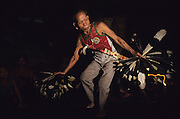 DAYAK DANCE, MALAYSIA. Sarawak, Borneo, South East Asia. Dayak, 'Kenyah', dances brave warrior dance on longhouse  verandah. Chasing away  evil spirits and recounting courageous hunting expeditions, 1991 <br /> <br /> Tropical rainforest and one of the world's richest, oldest eco-systems, flora and fauna, under threat from development, logging and deforestation. Home to indigenous Dayak native tribal peoples, farming by slash and burn cultivation, fishing and hunting wild boar. Home to the Penan, traditional nomadic hunter-gatherers, of whom only one thousand survive, eating roots, and hunting wild animals with blowpipes. Animists, Christians, they still practice traditional medicine from herbs and plants. Native people have mounted protests and blockades against logging concessions, many have been arrested and imprisoned.