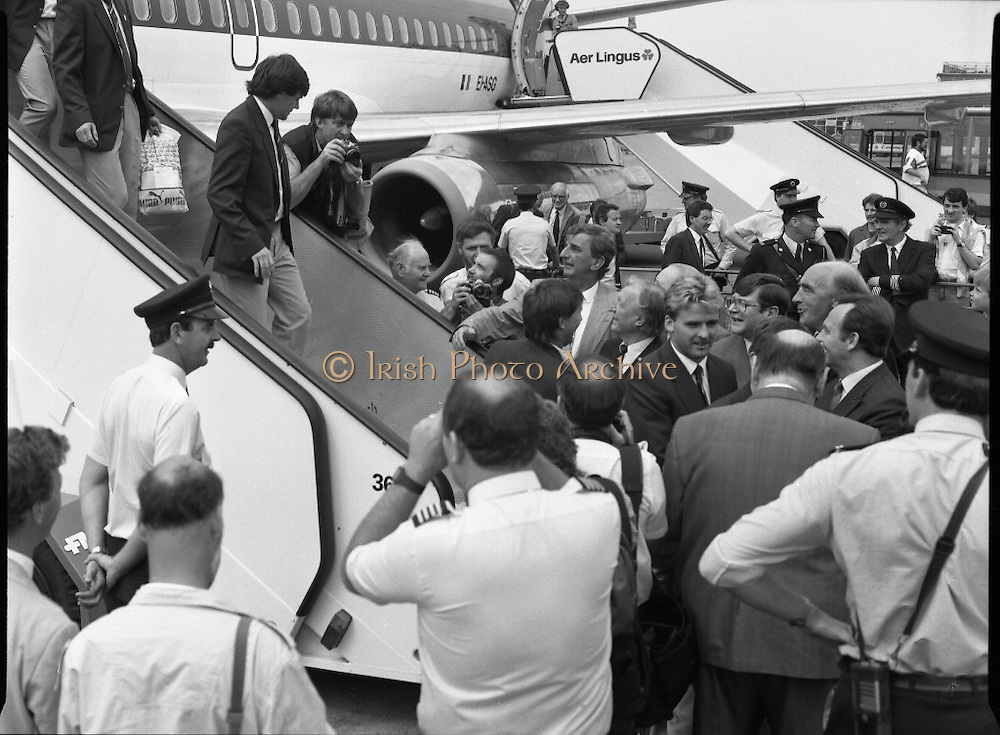 Irish Soccer Team Welcomed Home.   (R81)..1988..19.06.1988..06.19.1988..19th June 1988..After their great success in Germany in Euro 88, the Irish soccer team had a triumphant homecoming. An Taoiseach, Charles Haughey TD and his government were to the forefront of the welcome. Thousands of fans thronged the airport and all the approach roads in the hope of seeing the team. The full squad is as follows..1.GK.Packie Bonner. Celtic.2.DF.Chris Morris. Celtic.3.DF.Chris Hughton  Tottenham Hotspur.4.DF.Mick McCarthy. Celtic.5.DF.Kevin Moran. Manchester United.6.MF.Ronnie Whelan. Liverpool.7.MF.Paul McGrath. Manchester United.8.MF.Ray Houghton. Liverpool.9.FW.John Aldridge. Liverpool.10.FW.Frank Stapleton Derby County.11.MF.Tony Galvin. Sheffield Wednesday.12.FW.Tony Cascarino. Millwall.13.MF.Liam O'Brien. Manchester United.14.FW.David Kelly. Walsall.15.MF.Kevin Sheedy. Everton.16.GK.Gerry Peyton. Bournemouth.17.FW.John Byrne. Le Havre.18.FW.John Sheridan. Leeds United.19.DF.John Anderson. Newcastle United.20.FW.Niall Quinn. Arsenal..Image shows the Irish team being greeted by An Taoiseach,Charles Haughey TD, and members of government as they descend from the aircraft.