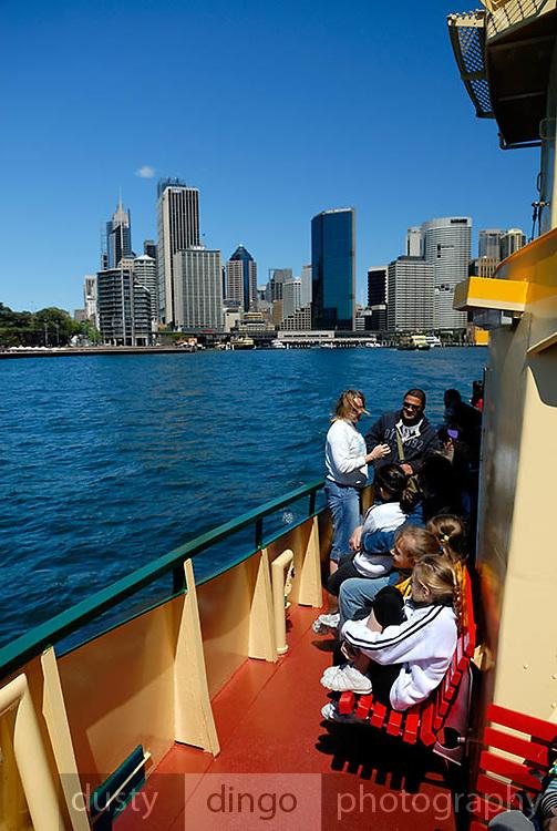 Passengers on deck of Sydney Ferry, Circular Quay skyline in background. Sydney, Australia