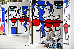 "© Licensed to London News Pictures. 04/08/2020. LONDON, UK.  Artist Anna Laurini works on her new artwork ""Urban Spinxes"".  Located outside a construction site just off Carnaby Street, the piece is  inspired by Pablo Picasso and Henri Matisse.  The construction company commissioned the artist to design something to cover up what would otherwise be bare wooden hoardings.  Photo credit: Stephen Chung/LNP"