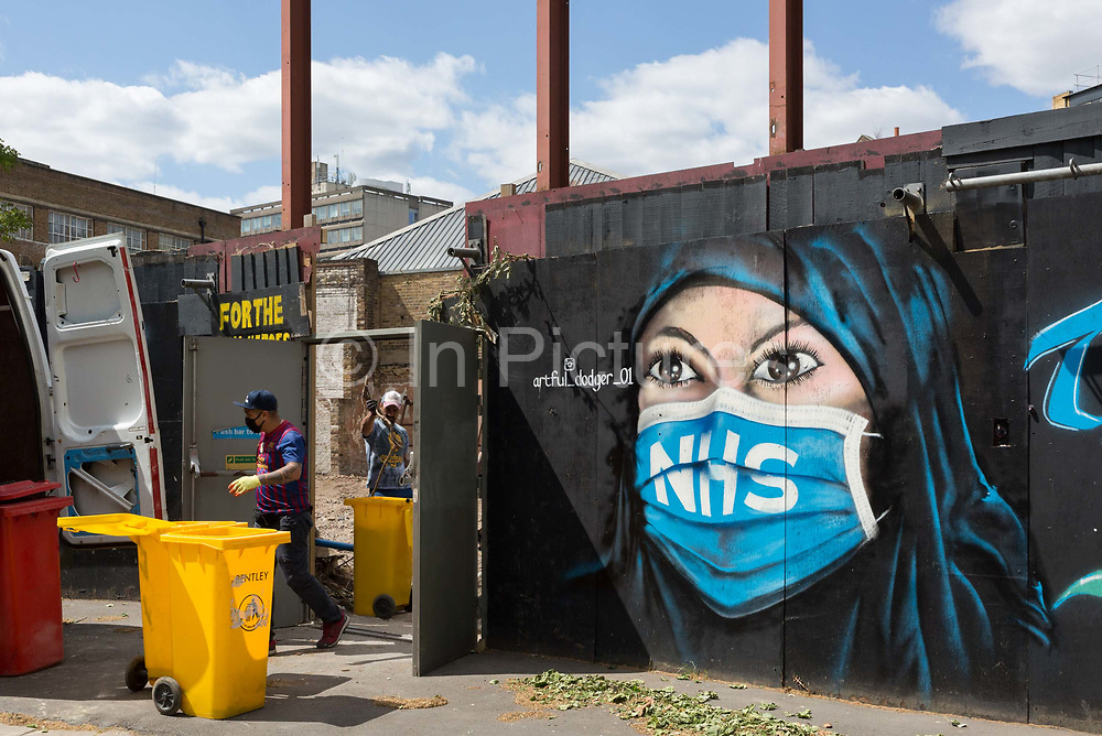 On the day that the UK death rate during the Coronavirus pandemic surpasses 40,000, including almost 10,000 care home residents, the highest rate in Europe, workmen clear a brownfield site next to a mural created by the anonymous street artist known as Artful Dodger after Charles Dickenss pickpocket character in Oliver Twist, of a Muslim NHS National Heath Service nurse wearing a surgical face mask, at Elephant & Castle in south London, on 121th May 2020, in London, England.
