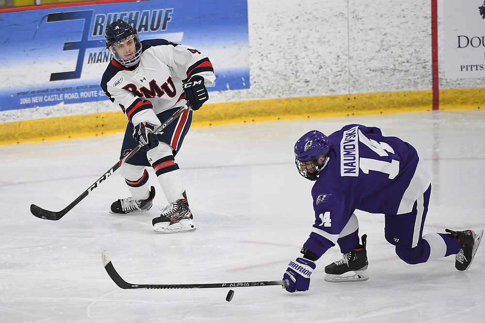 PITTSBURGH, PA - MARCH 12: Tyler Love #4 of the Robert Morris Colonials attempts a pass as Ryan Naumovski #14 of the Niagara Purple Eagles defends in the third period during Game One of the Atlantic Hockey Quarterfinal series at Clearview Arena on March 12, 2021 in Pittsburgh, Pennsylvania. (Photo by Justin Berl/Robert Morris Athletics)