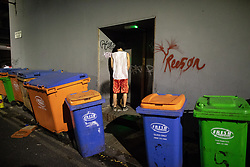 © Licensed to London News Pictures . 28/10/2018. Manchester, UK. A man urinates in a doorway amongst wheelie bins on Jerusalem Place in Manchester City Centre . Revellers on a night out , many in fancy dress , on the weekend before Halloween . Photo credit: Joel Goodman/LNP