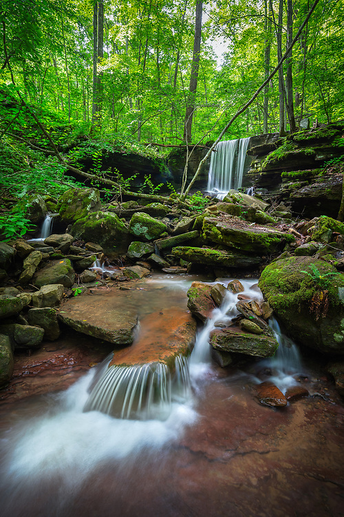 The falls of Big Branch in the New River Gorge of West Virginia flow gently down and around the rocks surrounded by lush greenery after heavy rains.