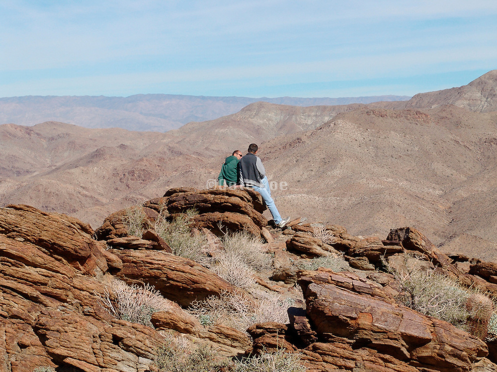 Two people on top of a mountain enjoying the view.