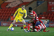 Jack Rudoni of AFC Wimbledon goes past Doncaster midfielder Matt Smith  during the EFL Sky Bet League 1 match between Doncaster Rovers and AFC Wimbledon at the Keepmoat Stadium, Doncaster, England on 26 January 2021.