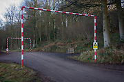 Height restriction caution sign and poles in a north Somerset woodland. Situates on a track on land in the south-west of England, we see the red and white striped structure with its caution sign attached, warning passing drivers of immediate danger. And yet, the dangerous cables carrying electricity is way above. But EU signage is now required for all public areas where low-level voltage is considered a hazard.