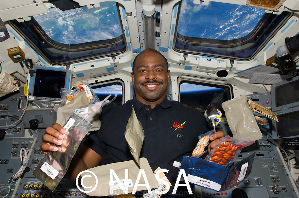 NASA astronaut Leland Melvin on the flight deck of the Space Shuttle Atlantis with his typical day's worth of food. (From the book What I Eat: Around the World in 80 Diets.) The caloric value of his day's worth of food in the month of February was 2700 kcals. He is 45 years of age; 6 feet tall; and 205 pounds. The early days of space travel were dominated by Tang, Space Food Sticks, and a variety of pastes squeezed from aluminum tubes—all designed to prevent the levitation of liquids and crumbs, which can be hazardous to the equipment. Over the years, space menus have become more palatable, and now astronauts can even enjoy fresh fruits for the first few days of a mission. The challenges of weightlessness extend to photography. Even with three fellow astronauts helping to wrangle Leland's floating food as shuttle commander Charles Hobaugh took the photo, all of the items in Leland's daily fare aren't clearly visible. Photo credit: NASA  MODEL RELEASED.