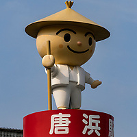 """Henro Pilgrim Figurine Welcome Sign - The Shikoku Pilgrimage is one of the most celebrated pilgrimages in the world. The trail of 88 temples circumnavigates the island of Shikoku. The entire route is about 1200 kilometers long which allows one to experience the abundant natural surroundings of Shikoku and gives many opportunities to mix with the local people - a rare chance to glimpse into the """"real"""" Japan. This pilgrimage provides the setting and situation to reflect on one's life and to ruminate on where one has been, where one is and where one is going.  Pilgrim's motives for making this voyage are varied. For example, some come for religious reasons, some to pray for healing or safety, or some in memory of those who have passed away.  Some come just to get away from regular life, others for recreation, or simply to spend time alone in reflection and to find oneself."""