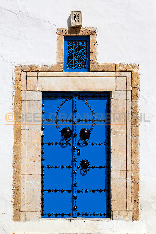 08-03-2014 Blue door with sand color, yellow brick door post and a white wall at the blue and white houses of Sidi Bou Said in Tunisia.