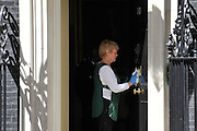 © licensed to London News Pictures. LONDON, UK  24/05/11. A member of the domestic staff polishes the door of No 10. Barack Obama, and Michelle Obama are met by David Cameron and Samantha Cameron in Downing Street during US President Obama's first State Visit to the United Kingdom. Please see special instructions. Photo credit should read Stephen Simpson/LNP