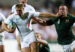 No mobile phone use, Internet sites may only use one image every five minutes during match:  England's Ben Cohen (L) fends off a tackle from South Africa captain Corne Krige during their Rugby World Cup match at the Subiaco Stadium, Perth, Australia. England won 25-6.