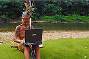 Even headhunters have to keep ahead. Iban elder and laptop, Iban tribe, former headhunters, rainforest Skrang River, Sarawak, Borneo, Malaysia.