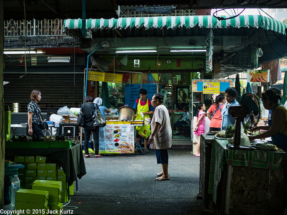 30 DECEMBER 2015 - BANGKOK, THAILAND:  People walk through the street market next to Bang Chak Market. The market is supposed to close permanently on Dec 31, 2015. The Bang Chak Market serves the community around Sois 91-97 on Sukhumvit Road in the Bangkok suburbs. About half of the market has been torn down. Bangkok city authorities put up notices in late November that the market would be closed by January 1, 2016 and redevelopment would start shortly after that. Market vendors said condominiums are being built on the land.           PHOTO BY JACK KURTZ