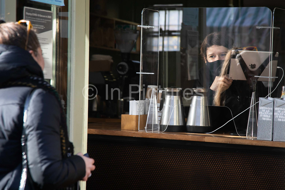 A woman in a coffee shop takes orders behind corona protective shield in Broadway Market during the second coronavirus national lockdownon on 7th of November 2020, East London, United Kingdom. The UK Government introduced a 4 week lockdown from November 5th - December 2nd to combat the coronavirus outbreak. It is the third day of the national lockdown restrictions mean that people are only allowed to meet outside, in pairs and only if keeping social distance. Only if they already live together or have formed a social bubble can they interact freely.