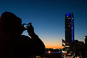 An unknown person snapping a picture of downtown Oklahoma City skyline with an iPhone.
