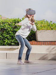 Girl wearing virtual reality glasses gesturing surfing position on terrace