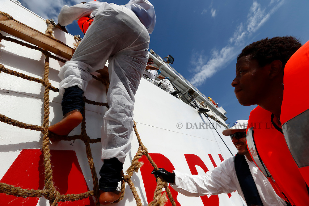 Rescued migrants climb onto the Italian Coast Guard Vessel Oreste Corsi from a Migrant Offshore Aid Station (MOAS) RHIB (rigid hulled inflatable boat) off the coast of Libya, August 3, 2015.  118 migrants were rescued by the MOAS ship MV Phoenix from a rubber dinghy some 20 miles (32 kilometres) off the coast of Libya on Monday morning. The Phoenix, manned by personnel from international non-governmental organisations Medecins san Frontiere (MSF) and MOAS, is the first privately funded vessel to operate in the Mediterranean.<br /> REUTERS/Darrin Zammit Lupi <br /> MALTA OUT. NO COMMERCIAL OR EDITORIAL SALES IN MALTA