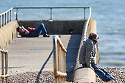 April 6, 2020, London, England, United Kingdom: People sunbathing  in Brighton Beach on Monday, April 6, 2020 - as British Prime Minister Boris Johnson was moved to intensive care after his coronavirus symptoms worsened in London. Johnson was admitted to St Thomas' hospital in central London on Sunday after his coronavirus symptoms persisted for 10 days. Having been in the hospital for tests and observation, his doctors advised that he be admitted to intensive care on Monday evening. The new coronavirus causes mild or moderate symptoms for most people, but for some, especially older adults and people with existing health problems, it can cause more severe illness or death. (Credit Image: © Vedat Xhymshiti/ZUMA Wire)