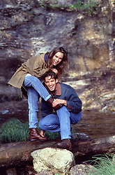 couple outdoors by a stream enjoying time together