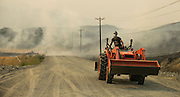 A resident with a tractor comes out to help put out the fire spreading from her neighbor's property on Soren Peterson Road at Johnson Creek Road, northwest of Omak, as wildfires burn central Washington August 20, 2015.<br /> <br /> Bettina Hansen / The Seattle Times