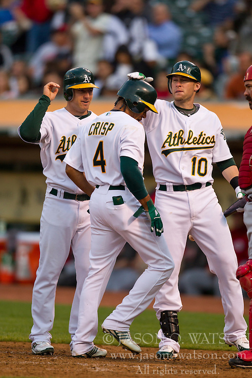 June 22, 2010; Oakland, CA, USA;  Oakland Athletics center fielder Coco Crisp (4) is congratulated by shortstop Cliff Pennington (left) and first baseman Daric Barton (10) after hitting a two run home run off of Cincinnati Reds starting pitcher Bronson Arroyo (not pictured) during the third inning at Oakland-Alameda County Coliseum.