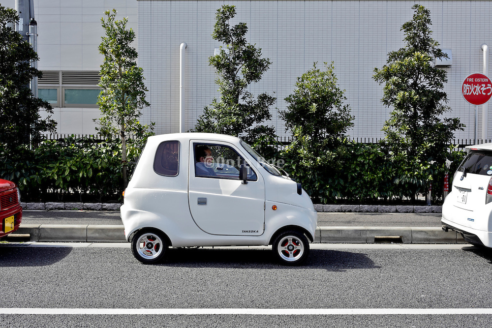 senior person sitting in a small single person disability vehicle Japan
