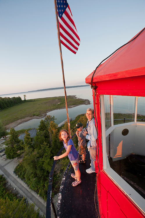 A family takes in the view from the gallery deck outside the lantern room of the St. Helena Island Lighthouse on Lake Michigan in the Straits of Mackinac.