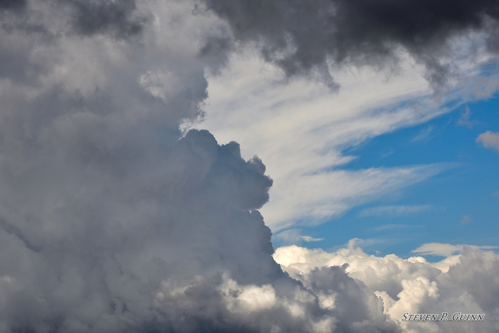 """I captured this, as well as """"Clouds Rolling in"""" and """"Dark Cloudscape"""", while I was in Rensselaer, Indiana on September 29th, 2016. I was most interested in these cloud formations because of the varying grey colors contrasting with white and black, while being set against vibrant blue sky. I was also drawn to the way the clouds are layered, and with each cloud formation being a different color, gives the image a natural depth. The way sun is shining behind the darker clouds, illuminating the lighter clouds in the background caught my eye as well.<br /> <br /> Printed on Hahnemühle German Etching paper. Limited to 150 productions per size.<br /> <br /> Framed prints available are in 18"""" x 12"""", 24"""" x 16"""", 30"""" x 20"""", and 36"""" x 24"""" sizes."""
