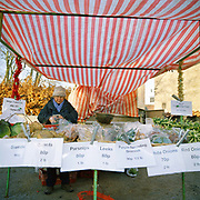 A farmer sells vegetables at a Christmas market in the picturesque village of Hovingham, North Yorkshire, UK